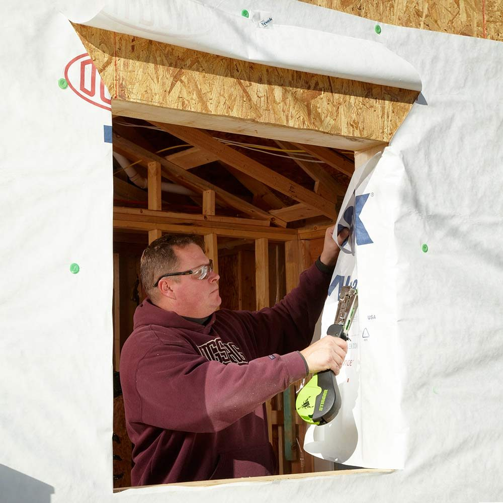 Installing house wraps around open window holes | Construction Pro Tips