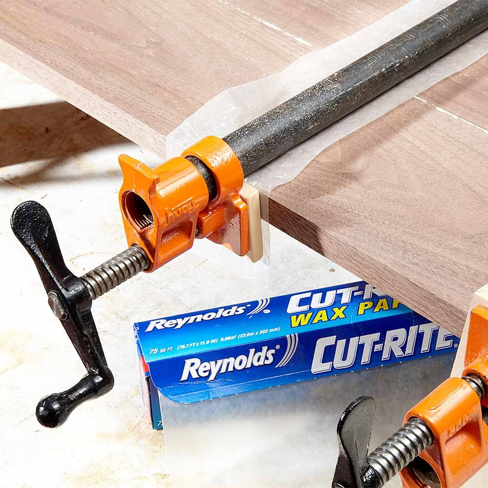 Laying down waxpaper to prevent clamp stains | Construction Pro Tips