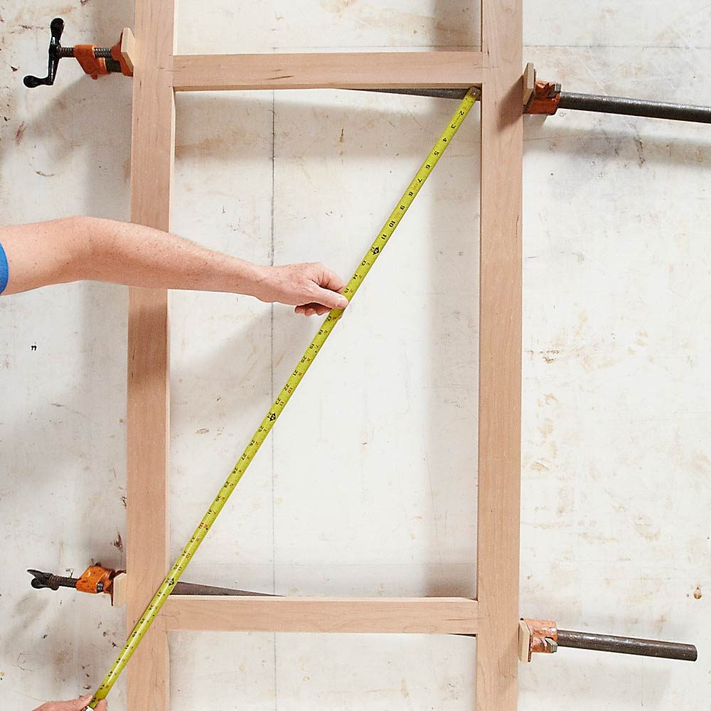 A man squaring a frame with clamps | Construction Pro Tips