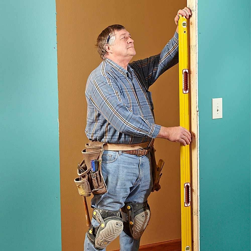 Man making sure that a door frame is level and plumb | Construction Pro Tips