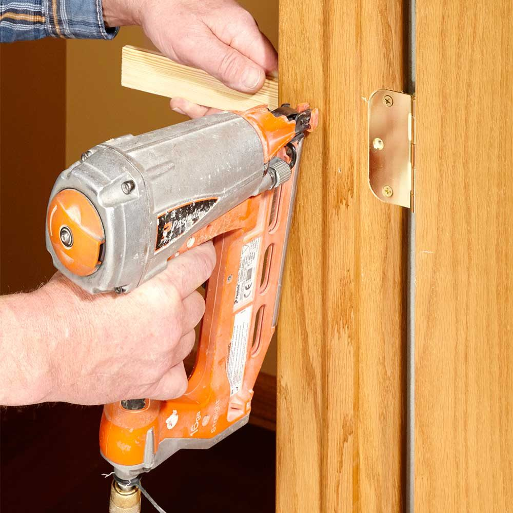 Shimming behind the edges of a door frame during installation | Construction Pro Tips