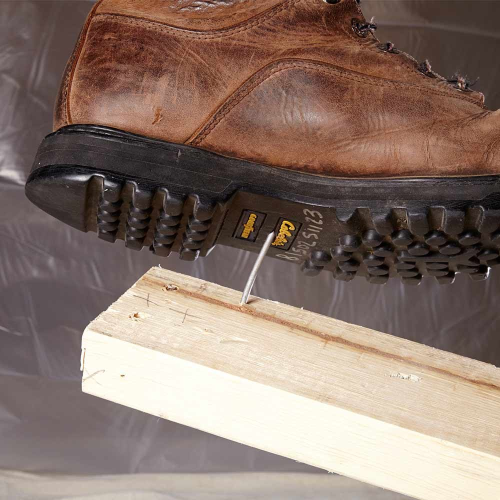 A boot about to step into a nail | Construction Pro Tips