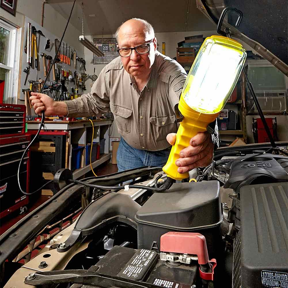 Man using a retractable floodlight to look under the hood | Construction Pro Tips