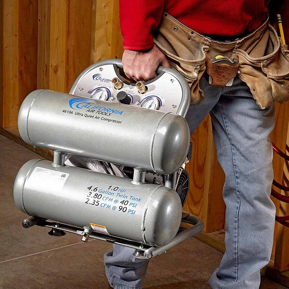A man carrying an air compressor | Construction Pro Tips