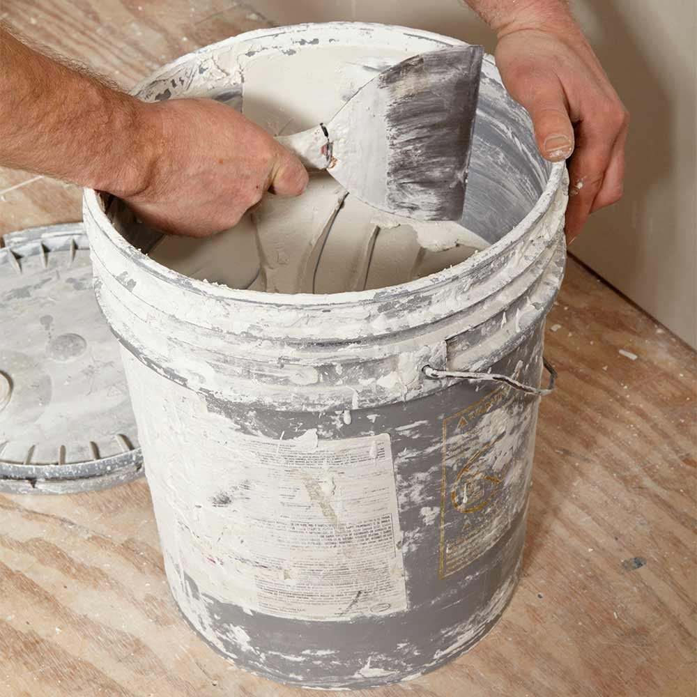 scraping the inside of the mud bucket | Construction Pro Tips