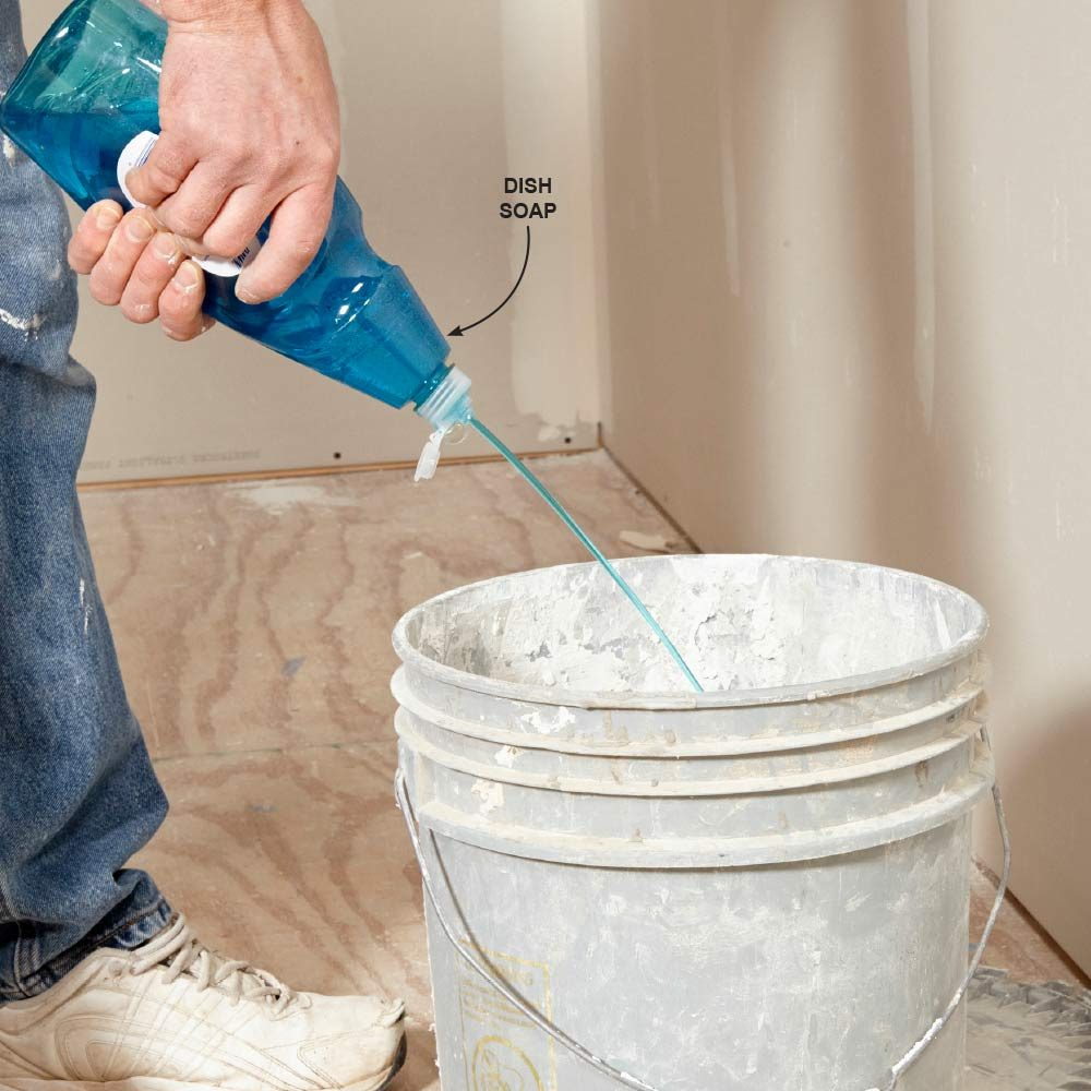 Squirting dish soap into a mud bucket | Construction Pro Tips