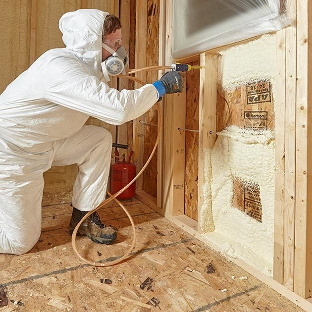 Man spraying insulation into cavity beneath window | Construction Pro Tips