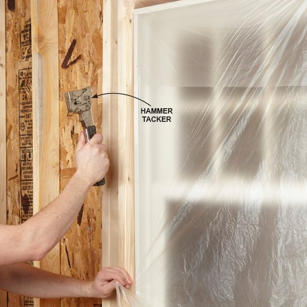 Using a stapler to cover a window with plastic | Construction Pro Tips