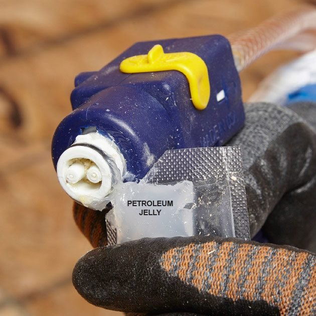 Squeezing petroleum jelly onto gun tip | Construction Pro Tips