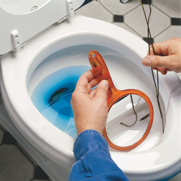 <b>Use a mirror and a coat hanger</b></br> Use a hand mirror to see the holes under the rim of the toilet. Bend a coat hanger flat and probe the tip into the holes to poke out any mineral deposits.