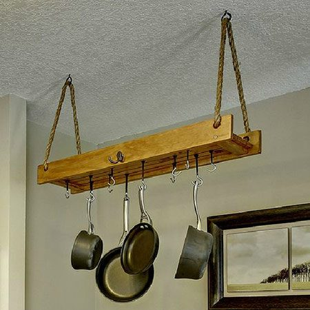 <b>Easy-to-Build Pots and Pans Organizer</b></br> <p>While some kitchens have a center island ideal for hanging a pot rack, others have to get a little more creative. This kitchen's narrow banister leading downstairs was dead, unused space—the perfect storage opportunity. Most store bought pot racks are too wide to fit this particular space, so we created a custom one with basic supplies from the hardware store. When you're thinking of your own pots and pans organizer ideas, keep in mind that you'll be hanging some pretty heavy stuff from it. The hanging rack needs to be stout enough to support the weight of multiple pots and pans.</p>