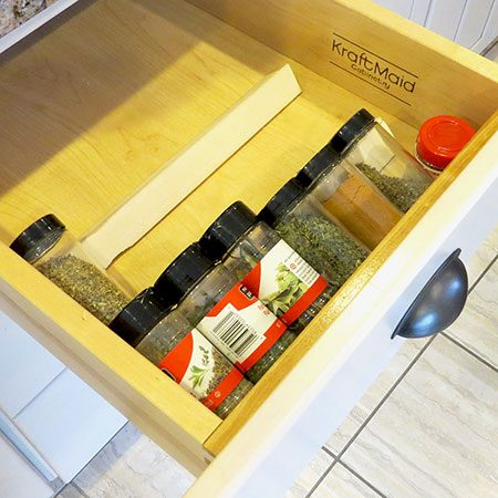 <b>Repurpose Paint Stirrers</b></br> <p>Hot glue paint stirrers (or or small scraps of wood) together at a 90-degree angle to tilt spices in a drawer. Run a line of hot glue along the bottom edges as well and let dry – this creates a gummy texture that holds the sticks in place in the drawer.</p>