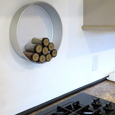 <b>Wall-Mounted Spice Storage</b></br> <p>Create a functioning focal point by mounting a deep metal cake pan to the wall. Drill a hole through the bottom of the pan and mount to the wall with an anchor. Lay spices in pan on their sides, and lesser-used spices will automatically roll towards the bottom over time.</p>