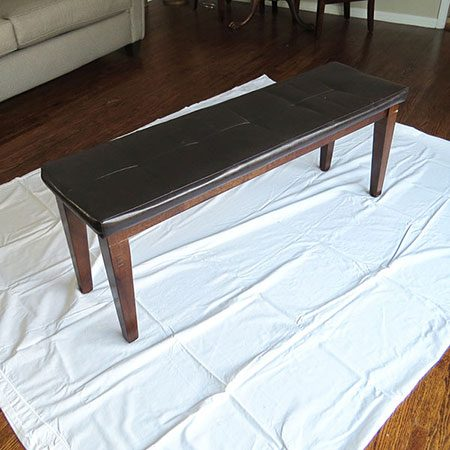 <b>Clean and Prep</b></br> The first step is to prep the area by wiping the leather clean with a damp cloth and laying a drop cloth down to protect your floors. Depending on your furniture piece, you might want to disassemble the furniture to separate leather parts or protect non-painted areas with painters tape.