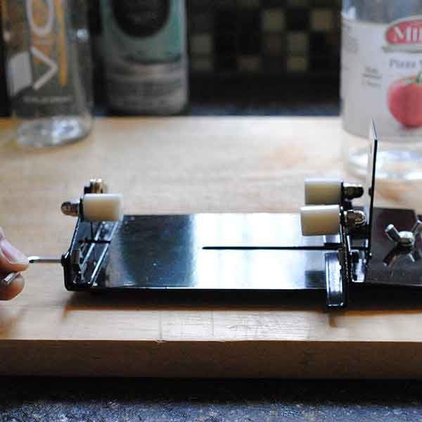 <b>Adjust the bottle cutter</b></br> <p> Follow the instructions on your bottle cutter to adjust the rollers, making sure the area to be cut rests on the scoring blade. When you have a good fit and the jar is snug against the blade, rotate it in a counterclockwise direction. As the blade hits the glass, you should hear a scraping sound. When the score has etched completely around the bottle, you might hear a crunch. A dusting of glass power might land on your cutter, so watch your fingers.</p>