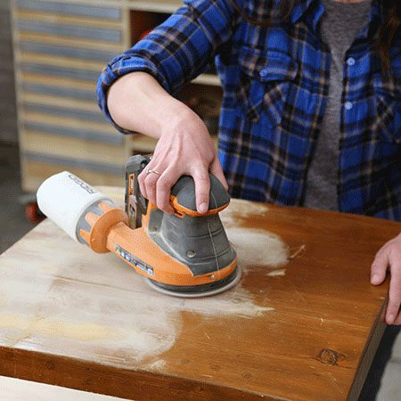 <b>Sand the Surface</b></br> <p>Sand the table to remove the old finish and smooth out any imperfections in the wood. Wipe off the dust with a damp cloth.</p>