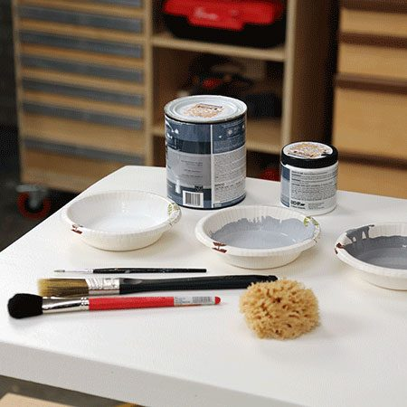 "<b>Mix Paint Colors</b></br> <p>In separate <a href=""https://www.familyhandyman.com/painting/tips/plastic-liner-to-keep-a-clean-paint-bucket/view-all#step1"" target=""_blank"">containers</a>, mix white and black paint to create two different shades of gray. Also, keep a small container of the white nearby. Add a couple of teaspoons of water to all colors to thin them out.</p> <p> <em>The following steps can be completed in one sitting; no need to let the paint dry between layers.</em></p>"