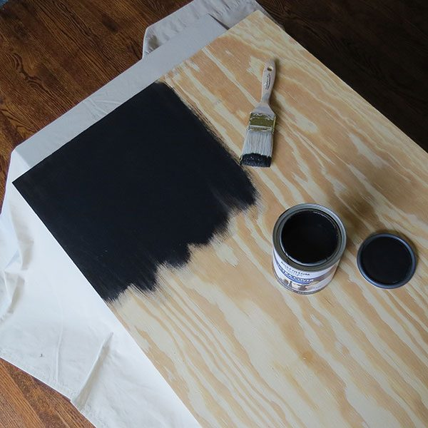 <b>Paint Plywood</b></br> <p> Next, cover the front side of plywood in black or dark paint. Spray, latex or stain will do the trick. The dark color will contrast against the logs, and create a false depth to the insert. Let dry.</p>