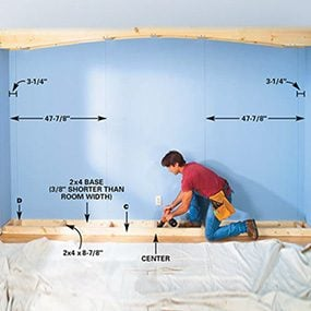 Assemble the base of the built-in bookcase and fasten it in place.