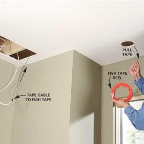 Photo 7: Use a fish tape reel to pull cables through joist spaces.