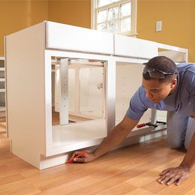 How to install kitchen cabinets family handyman for Wood floor 90 degree turn