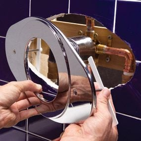 Add the cover plate to complete the shower faucet installation.