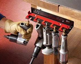This air tool holder has a latch to keep the tools secure.