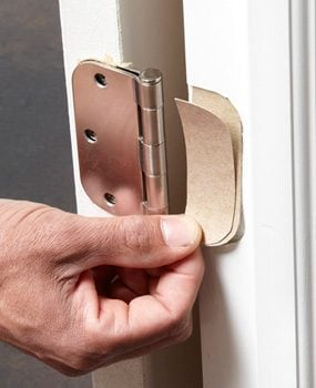 Use cardboard shims in the bottom hinges to help fix a sagging or sticking door.
