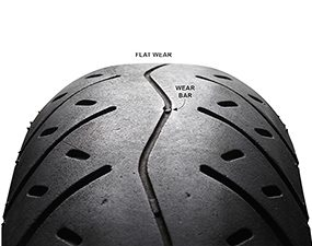 Photo showing a motorcycle tire with uneven wear and a partially worn wear bar.