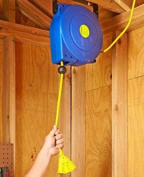 Retracting extension cord reel