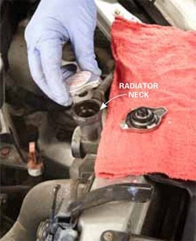 Radiator cap being replaced; old radiator cap is ling to the side on a rag.