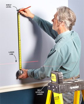 Man measuring from a line-level's beam to locate a shelf.