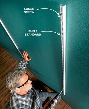 Shelf standard hanging from a loosely attached screw on top; shows how gravity makes the standard hang plumb.