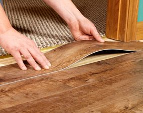 A plank being put into place by bending the middle up, essentially shortening the plank so it fits under the doorjamb.