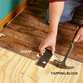 How to install luxury vinyl plank flooring the family handyman plank being tapped into place under a doorjamb solutioingenieria Image collections