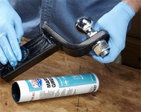 Applying marine grease to a trailer hitch ball mount.