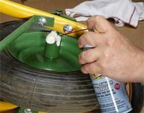 Spraying aerosol white lithium grease on a wheelbarrow wheel.
