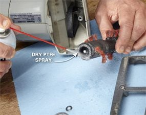 Spraying dry PTFE lube on vacuum cleaner parts.