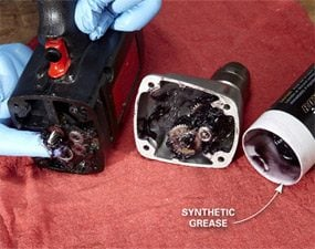 Spreading synthetic grease on power-drill drive gears.