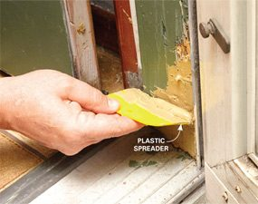 Using a spreader to apply wood filler to a screen door jamb when repairing a screen door.