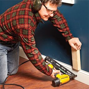 Forcing trim into place with a block before using a finish nailer.