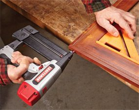 Using a finish nailer to put assemble prefinished parts.
