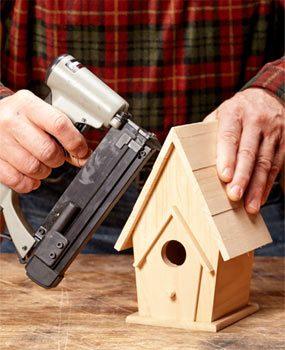 Using a pin nailer to assemble a birdhouse.