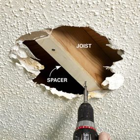 Shimming an exposed joist when covering a popcorn ceiling with drywall.
