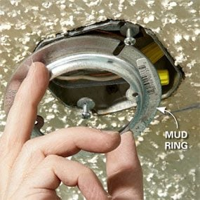 Installing a mud ring  when covering a popcorn ceiling with drywall.