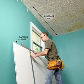 Measuring and cutting drywall sheet when covering a popcorn ceiling with drywall.