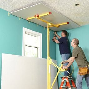 Using a drywall lift when covering a popcorn ceiling with drywall.
