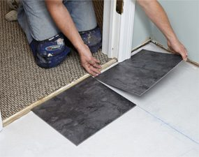 Carefully fit luxury vinyl tile under door jambs and casing.