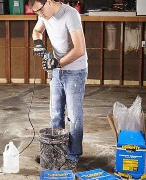 Mixing concrete resurfacer while resurfacing a garage floor.