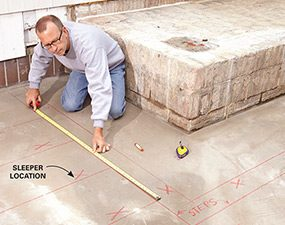 Mark the sleeper locations for the deck on the concrete patio.
